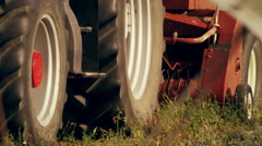Close-up shot of the bottom part of a tractor as it gathers hay Stock Footage