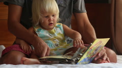Little girl turns over pages of book on father's knees on sofa Stock Footage