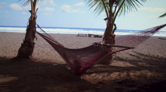 Someone swings in a hammock and looks at beach with dog - stock footage