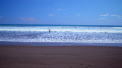 Long-distance footage of someone playing in ocean waves Stock Footage