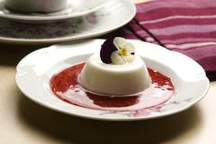 Vanilla panna cotta with berry sauce and spring flower - stock photo