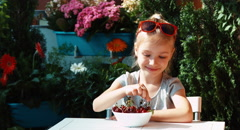 Girl eating a cherry. Child eating berries and admires them and looking Stock Footage