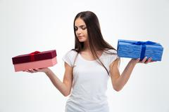 Woman making choice between two gift boxes - stock photo