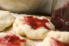 Dough with marmelade on wooden board - stock photo