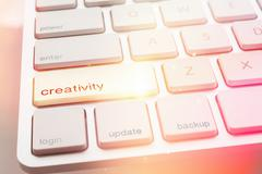 Light from CREATIVITY  button of computer keyboard - stock photo