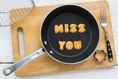 Letter biscuits word MISS YOU and cooking equipments. - stock photo