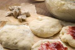 Dough with marmelade on wooden board Stock Photos