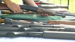 4K man handling several guns on table Stock Footage