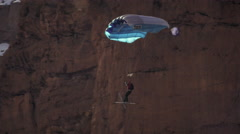 Slow-motion shot of base jumper going in for landing. Stock Footage