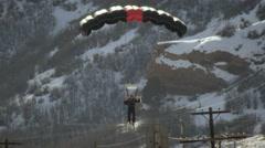 Slow motion shot of a base jumper landing on a ski slope, wearing skis. Stock Footage