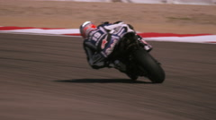 Slow motion shot of motorcycle racer turning a curve and coming very close to Stock Footage