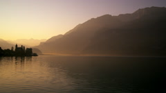 Static shot of silhouetted buildings over water at dawn Stock Footage