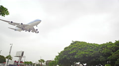 Plane flying over LAX welcome sign and trees Stock Footage