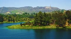 Long-distance static shot of reservoir, hills bearing Hollywood sign, houses - stock footage