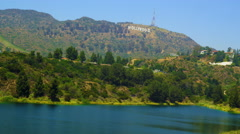 Pan of reservoir, hills bearing Hollywood sign, houses - stock footage