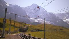 Swiss railway in front of Alps in Grindelwald, Switzerland Stock Footage