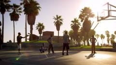 Slow motion shot of men playing basketball near Venice Beach, California filmed - stock footage