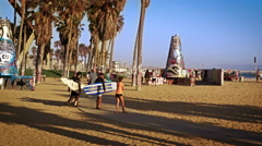 Slow motion shot of three surfers carrying surfboards walking near Venice Beach, Stock Footage