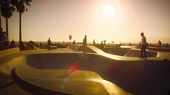 Slow motion shot of skateboarder and rollerblader in skate park near Venice Stock Footage