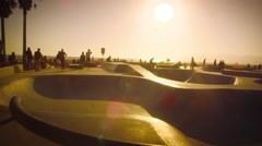 Slow motion lens flare shot of skateboarders on ramp near Venice Beach, Stock Footage