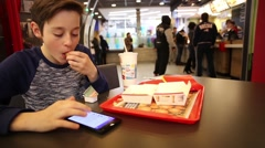 Teenager Eating French Fries and Using Smartphone - stock footage