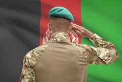 Dark-skinned soldier in hat facing national flag series - Afghanistan Stock Photos