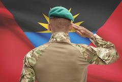 Dark-skinned soldier in hat facing national flag series - Antigua and Barbuda - stock photo