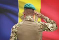 Dark-skinned soldier in hat facing national flag series - Andorra - stock photo