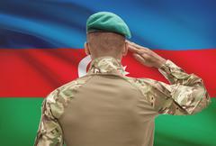 Dark-skinned soldier in hat facing national flag series - Azerbaijan - stock photo