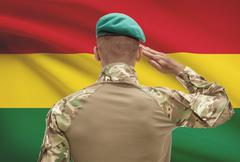 Dark-skinned soldier in hat facing national flag series - Bolivia Stock Photos