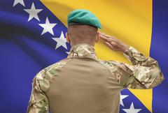 Stock Photo of Dark-skinned soldier in hat facing national flag series - Bosnia and Herzegov