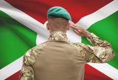 Dark-skinned soldier in hat facing national flag series - Burundi - stock photo