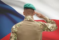 Dark-skinned soldier in hat facing national flag series - Czech Republic Stock Photos