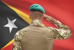 Dark-skinned soldier in hat facing national flag series - East Timor - stock photo