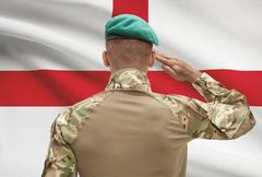 Dark-skinned soldier in hat facing national flag series - England - stock photo