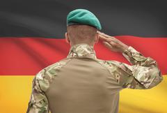 Dark-skinned soldier in hat facing national flag series - Germany - stock photo