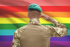Dark-skinned soldier in hat facing national flag series - LGBT people Stock Photos