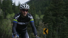 Man road biking through mountains Stock Footage