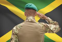 Dark-skinned soldier in hat facing national flag series - Jamaica Stock Photos