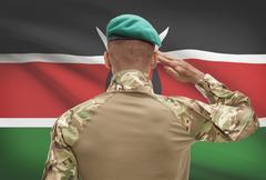 Dark-skinned soldier in hat facing national flag series - Kenya - stock photo