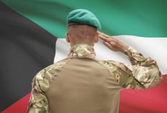 Dark-skinned soldier in hat facing national flag series - Kuwait Stock Photos