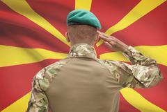 Stock Photo of Dark-skinned soldier in hat facing national flag series - Macedonia