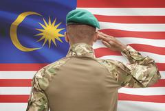 Dark-skinned soldier in hat facing national flag series - Malaysia - stock photo