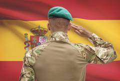 Dark-skinned soldier in hat facing national flag series - Spain Stock Photos