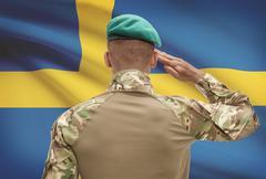 Dark-skinned soldier in hat facing national flag series - Sweden - stock photo