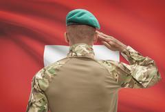 Dark-skinned soldier in hat facing national flag series - Switzerland Stock Photos