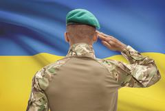 Dark-skinned soldier in hat facing national flag series - Ukraine Stock Photos