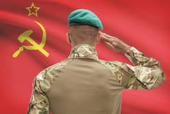 Dark-skinned soldier in hat facing national flag series - USSR - Soviet Union - stock photo