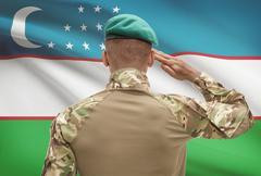 Dark-skinned soldier in hat facing national flag series - Uzbekistan - stock photo