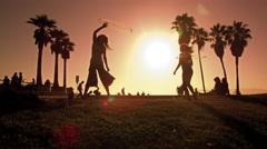 Lens flare shot of people strolling near Venice Beach, California filmed in slow Stock Footage